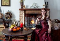 Young girl in a vintage dress by the fireplace stock photo