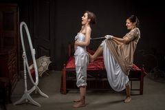 A young girl in a vintage dress tightens her corset to his girlfriend, joking format. Added a small grain, imitation of film stock photo