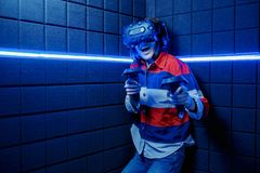 Girl in a virtual reality helmet scared. A young girl in a virtual reality club plays scary video games in a virtual reality helmet. Emotions of fear stock image