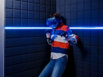 Girl in a virtual reality helmet scared. A young girl in a virtual reality club plays scary video games in a virtual reality helmet. Emotions of fear royalty free stock image