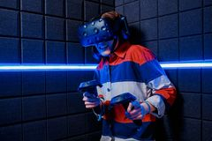 Girl in a virtual reality helmet scared. A young girl in a virtual reality club plays scary video games in a virtual reality helmet. Emotions of fear royalty free stock photo