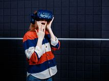 Young girl in a virtual reality helmet in the game room. A young girl in a virtual reality helmet in the game room is playing a video game. Fright emission royalty free stock photo