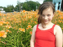 Young Girl With Vivid orange Flowers. With soft yellow highlights against green grass royalty free stock photography