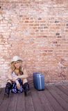 Young Girl Waiting. A young lady sits against a brick wall with her luggage. A lot of good negative space for your message stock images