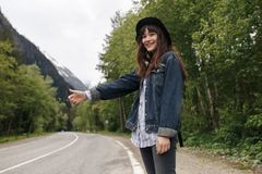 Young girl waiting for the car on the background of the mountains hitch-hiking royalty free stock image