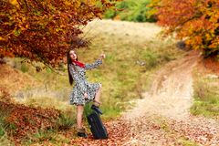 Young girl waiting on a country road with her suitcase. Stock Photos