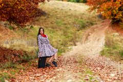 Young girl waiting on a country road with her suitcase. Royalty Free Stock Images