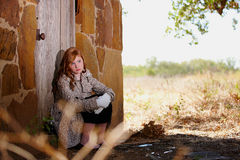 Young girl waiting at doorstep. Young redheaded girl sitting on the stoop waiting at the door Stock Photos