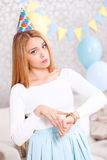 Young girl waiting for friends at birthday party. Friends are late. Young beautiful blond girl wearing cone cap pointing at her watches with a sad face because Royalty Free Stock Photography