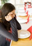 Young girl waiting in a restaurant. Brunette young girl waiting at a table in a restaurant, with an empty plate in front of her Royalty Free Stock Images