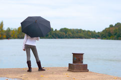 Young girl waiting on the river dock Stock Photography