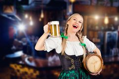 Young girl waitress oktoberfest in national costume with a mug o. F beer in her hand in pub. St. Patrick`s Day stock image