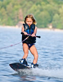 Young Girl on Wakeboard. A young girl riding her wakeboard. 7 years old royalty free stock photography
