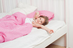 Young girl wakes up in the morning. In the bedroom Stock Images