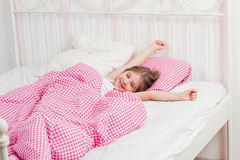 Young girl wakes up in the morning. In the bedroom Stock Image