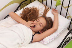 Young girl waking up in her bed. Stretching and yawning Royalty Free Stock Image