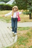 Young girl walk on curb. Jeans, ping bag.  Royalty Free Stock Image