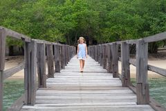 Young girl walk by wooden pier on sea sand beach royalty free stock images