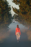 Young girl walking. A young girl walking in the early morning fog Stock Images