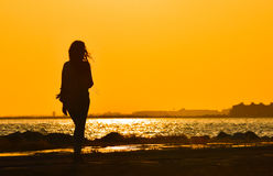 Young girl walking alone near seashore at sunset, silhouette. Stock Photos