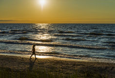 Young girl walking along beach, gold sunset. Young girl walking along the beach of Lake Huron, blue waves, gold evening time, Pinery Provincial Park stock photos