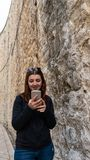 Young girl walking through ancient narrow streets and typing a smart phone. Beautiful red head woman talking with her boyfriend stock photography