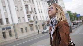 A young girl walking around the city. A young student with blond hair is walking around the city. Slow motion stock footage