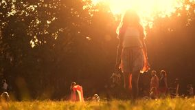 Young girl walking barefoot on the grass holding her high heel shoes in hand. Orange color Stock Photos