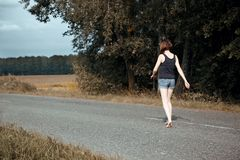 Young girl walking barefoot on the road, the concept of summer and travel Royalty Free Stock Images