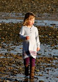Young girl walking on beach Stock Images