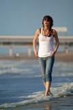 Young girl walking on a beach Stock Photos