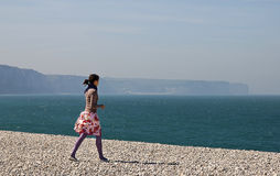 Young girl walking on the beach Stock Photography