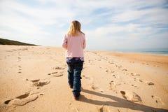 Young girl walking on beach Stock Photo