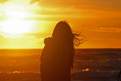 Young girl walking on beach. Young girl silhouette walking on the beach at summer royalty free stock images