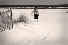 Young Girl Walking on Beach. Old fashioned photo of child holding pail on beach royalty free stock image