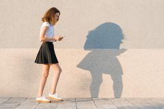 Young girl walking with big steps and reading text on mobile phone, gray outdoor wall background, copy space.  royalty free stock photo