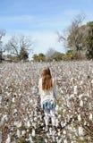 Young girl walking through cotton field. Royalty Free Stock Photos