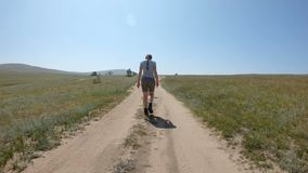 Young girl walking on a country road. Back view, gimbal shot, slow motion stock footage