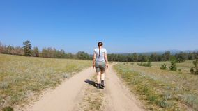 Young girl walking on a country road. Young girl with braid in shorts and t-shirt walking on a country road. Back view, gimbal shot, slow motion stock footage