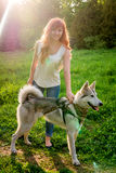 A young girl walking a dog in the park Royalty Free Stock Image