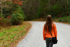 Young girl walking down the road. Royalty Free Stock Photo