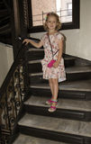 Young girl walking down stairs holding the rail Stock Photo
