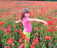 Young girl walking into field of poppies. A young girl walking into field of poppies Royalty Free Stock Images