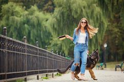 A young girl is walking with a dog in the park. Royalty Free Stock Photos