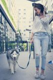 Young girl walking with her dog through city. Royalty Free Stock Photography