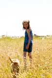 Young girl walking her dog through a field grass Royalty Free Stock Images