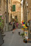 Young girl walking her dog through narrow streets in Corniglia royalty free stock photography