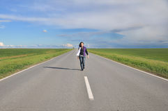 Young girl walking on the highway Stock Images