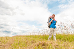 Young girl walking in meadow with backpack on. Royalty Free Stock Images