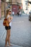 Young girl walking in the old town. Young adults on tourist travel in summer. Stock Photos